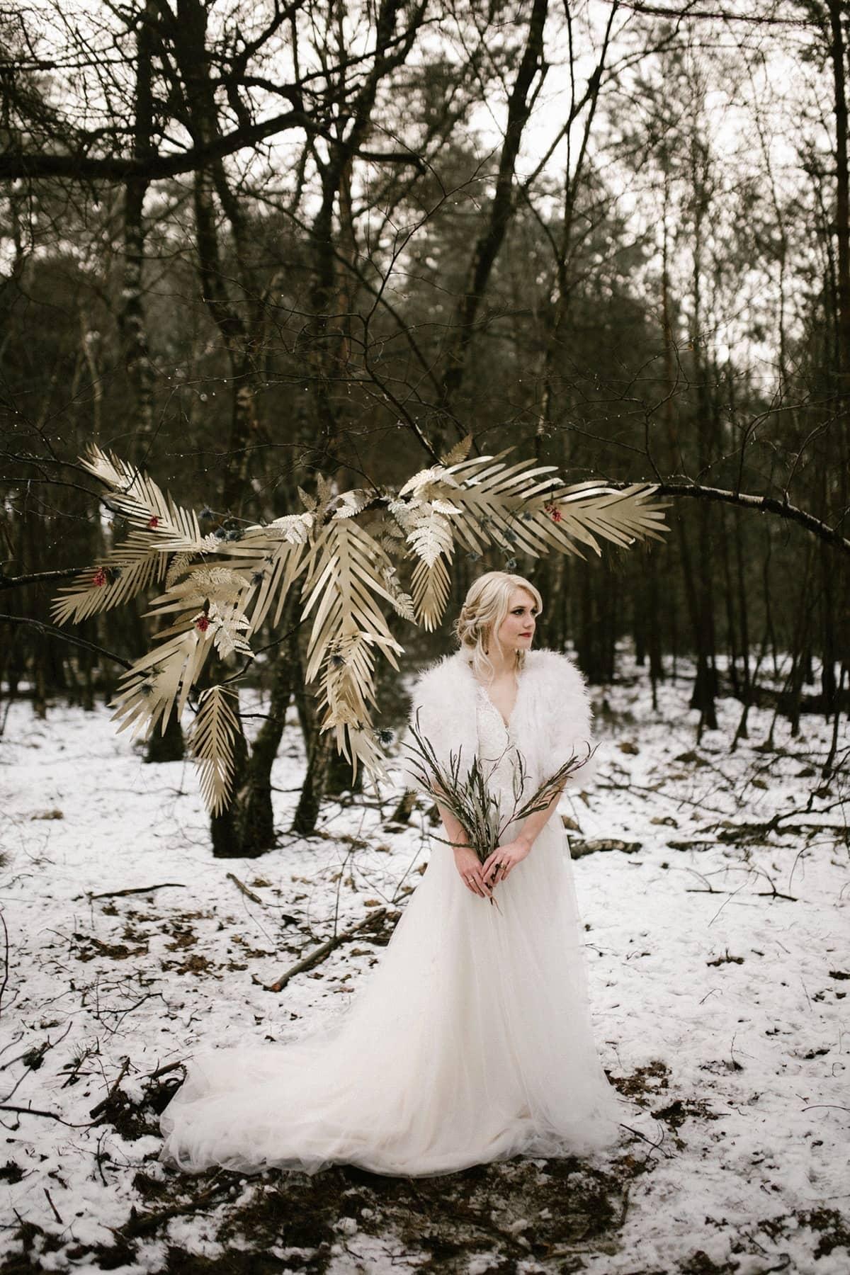 sprookjesachtige bruiloft in de sneeuw gouden backdrop